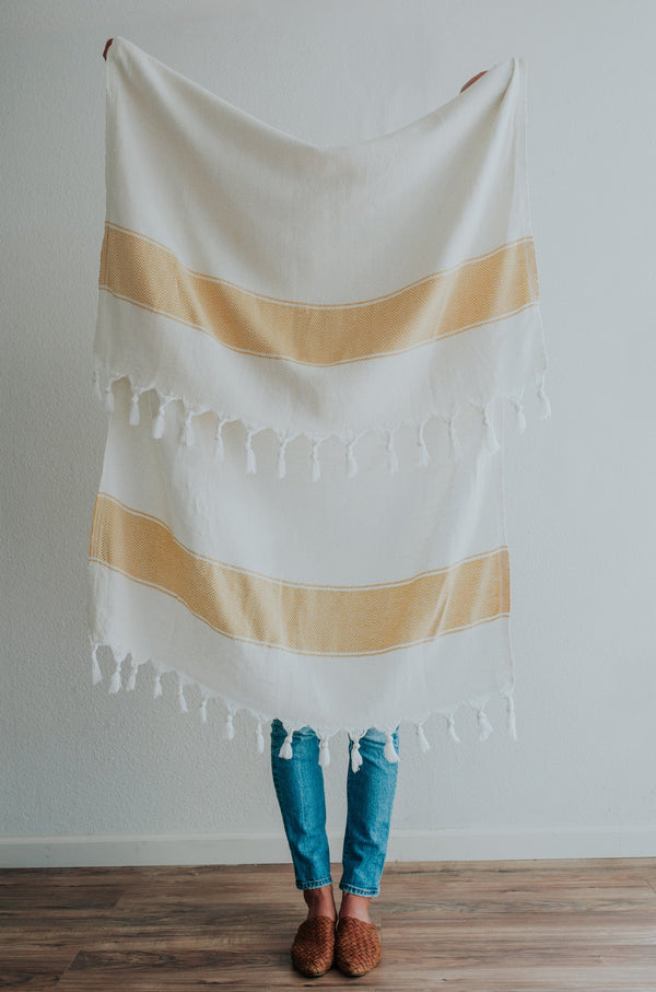 Person holding Bon Ton Studio Bodie Turkish Towel in Marigold color in front of wall