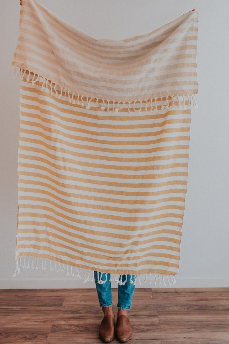 Person holding Bon Ton Studio Ulla Turkish Towel in Mustard color in front of wall