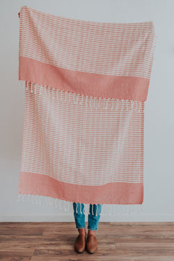 Person holding Bon Ton Studio Mila Turkish Towel in Poppy color in front of wall