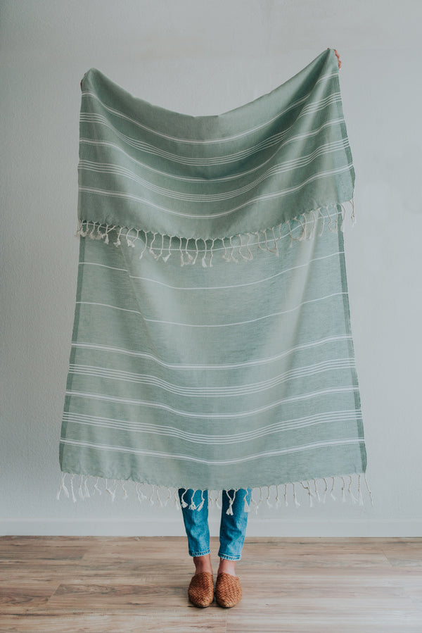 Person holding Bon Ton Studio Thea Turkish Towel in Sage color in front of wall