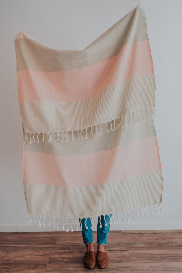 Person holding Bon Ton Studio Flora Turkish Towel in Salmon color in front of wall