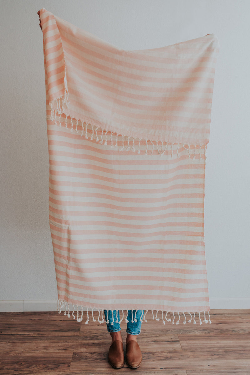 Person holding Bon Ton Studio Ulla Turkish Towel in Salmon color in front of wall