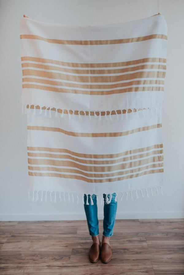 Person holding Bon Ton Studio Greta Turkish Towel in Marigold color in front of wall