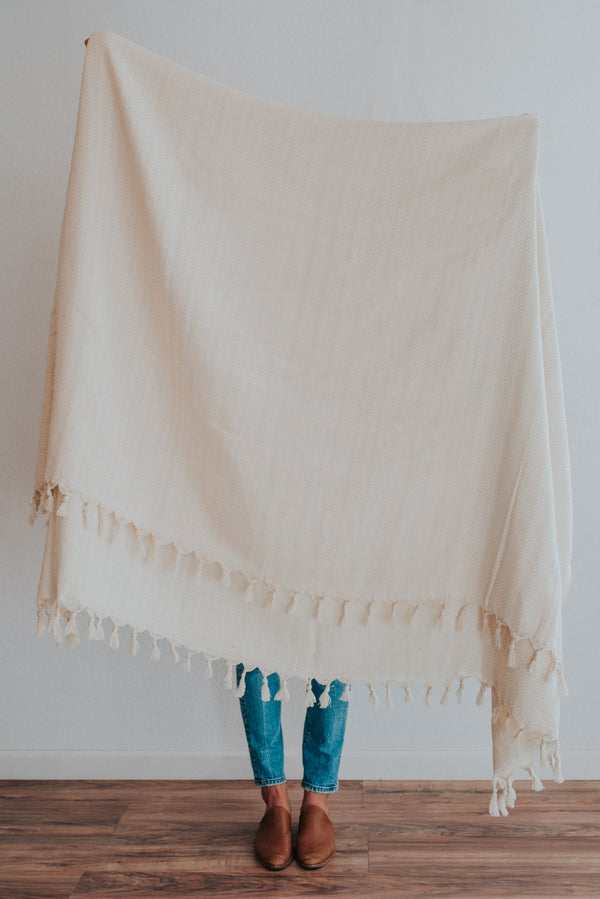 Person holding a light cream vanilla turkish throw blanket