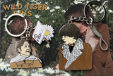 Harold Keychain with noose dongle, Maude Keychain with Peace Picket sign and Daisy dongle on a Postcard featuring a scene from the movie Harold and Maude