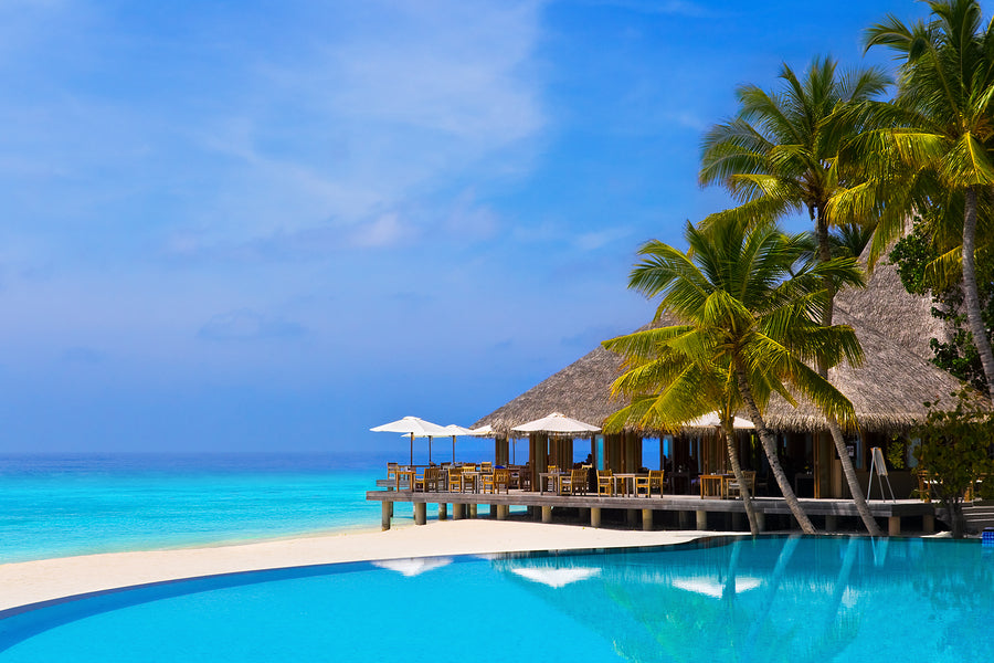 Cafe and pool on a tropical beach - travel background