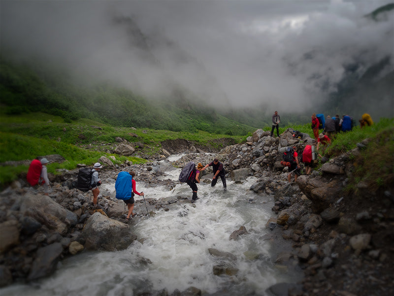 Hikers group cross the mountain river ford
