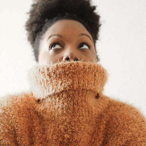 Black woman with afro puff looking up pulling her jumper over her face