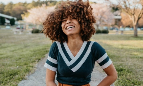 smiling happy woman with afro light brown hair and green top