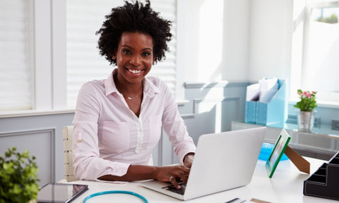 Afro hair care for essential workers: black female doctor with afro hair working at a desk