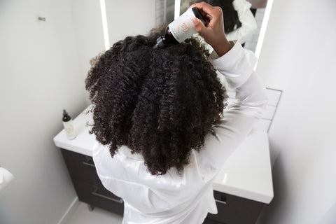 Itchy scalp: back view of black woman applying oil to scalp