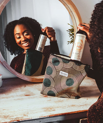 How to celebrate Valentine's Day in lockdown: afro-haired woman taking out Afrocenchix product out of African print bag