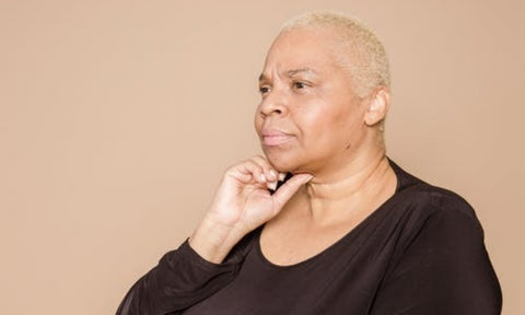 Afrocenchix article how menopause affects hair health: older black woman with bleached blonde short hair looking pensive .jpeg