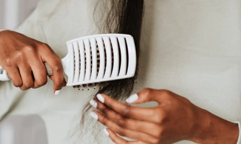 Afrocenchix how to detangle your natural hair: close up of a black woman detangling her hair with a brush