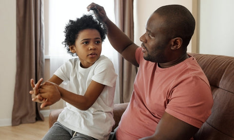 Afrocenchix how to detangle your natural hair: father and child sitting together detangling and combing curly afro hair