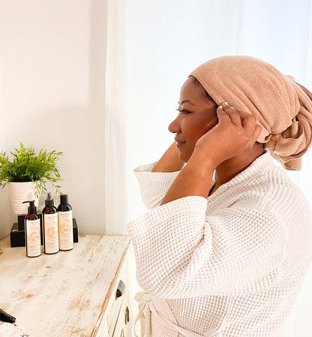 the side view of a woman adjust the towel on her head