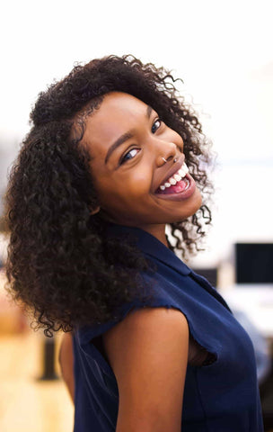 Smiling black woman with a braid out - Afrocenchix transitional hairstyles inspo article
