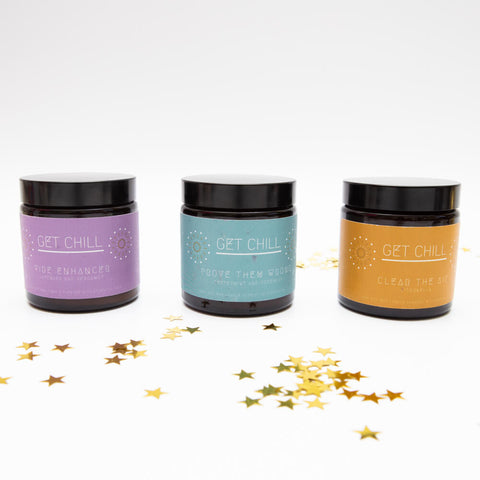Set of three candles in amber jars with purple, teal and yellow labels