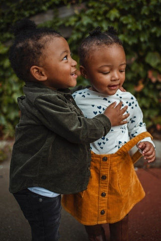 Two cute black toddlers standing together