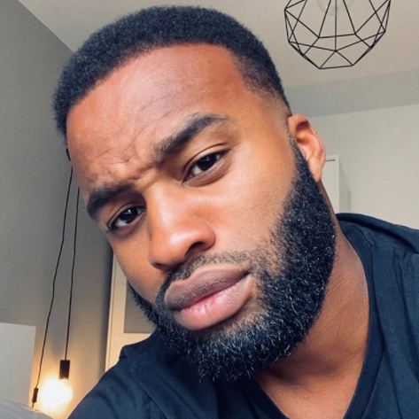 black man with short hair and beard wearing black