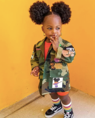 back to school hairstyles: young black girl with two cute afro puffs