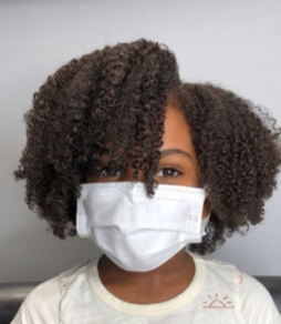 back to school hairstyles: young black girl wearing a mask with a cute wash and go afro