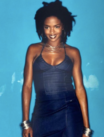 Lauryn Hill smiling with dreaklocks wearing a denim outfit