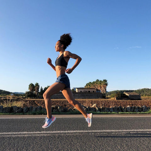 Side profile of a black woman running on a road