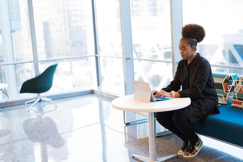 Black professional woman working on laptop with afro puff hairstyle