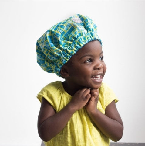 Afrocenchix essential Tips For Looking After Your Child's Kinks, Coils & Curls: Happy young black child wearing a yellow up and a satin lined Afrocenchix Bonnet