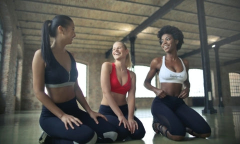 Three women kneeling and smiling in a workout studio