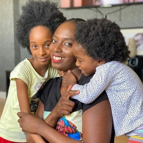 Afrocenchix essential Tips For Looking After Your Child's Kinks, Coils & Curls: Happy black mum being cuddled by her two young children with natural hair