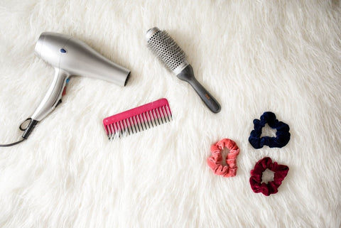 Afrocenchix essential  Tips For Looking After Your Child's Kinks, Coils & Curls: Hair styling tools such as barrel brush and hair dryer laid out on a white furry cloth