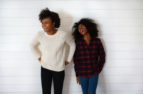 two black women with natural hair laughing