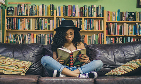 Afro hair girl wearing a hat, reading on a couch