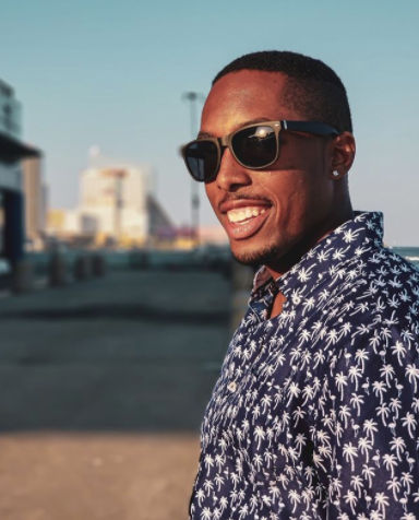 Black man with short buzz cut smiling with sunglasses