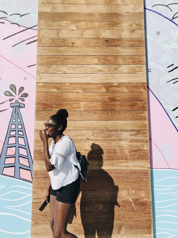 Black woman standing in front of colourful wall in the summer