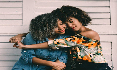 Two afro hair women hugging