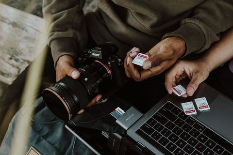 Close up of hands holding a camera, SD cards and a laptop