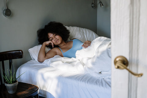 Woman with natural hair lying in bed