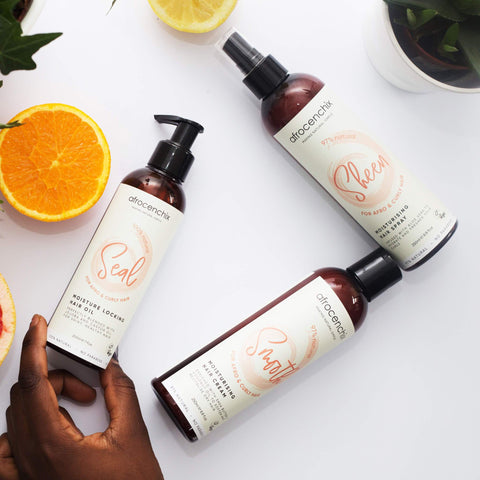 A hand touching the Afrocenchix moisture surge set with citrus fruit