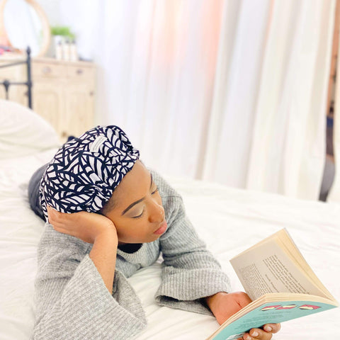 Afrocenchix How To Effectively Moisturise Afro Hair: Black woman lying on bed with satin bonnet reading a book
