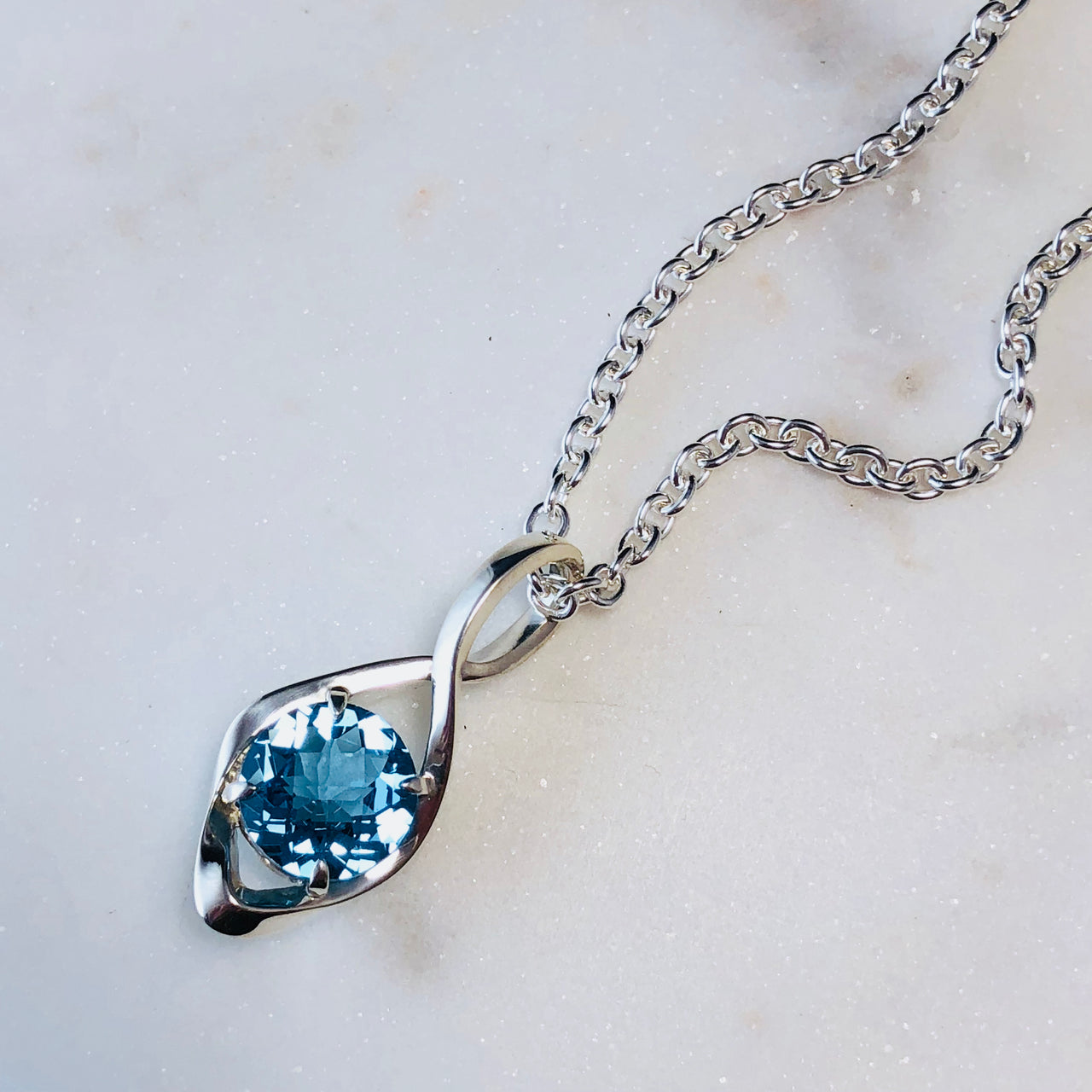 Sterling Silver Blue Topaz Infinity Pendant.