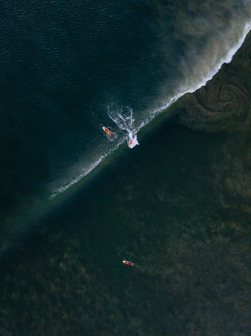 Aerial photo of surfers and wave breaking in Tamarindo Costa Rica. Aerial surfer art pictures photographed by Kristen M. Brown, Samba to the Sea for The Sunset Shop.