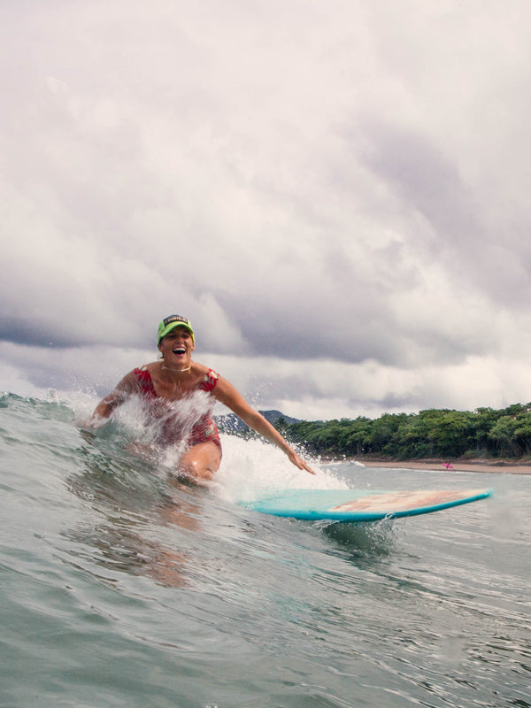Surfer girl laughing while surfing in Tamarindo, Costa Rica. Kristen M. Brown, Samba to the Sea.