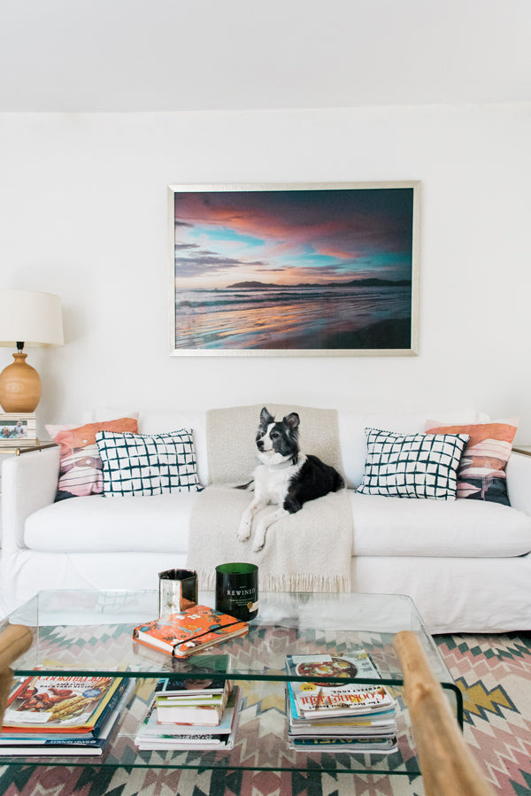 Beautiful sunset print hanging over a white coach. Boho chic inspired living room with a Lulu and Georgia rug. The Sunset Shop by Samba to the Sea.