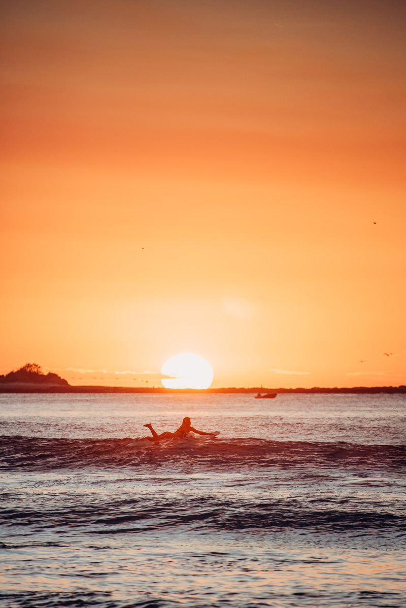 Female surfer during sunset in Tamarindo Costa Rica during sunset. Photographed by Kristen M. Brown, Samba to the Sea for The Sunset Shop.