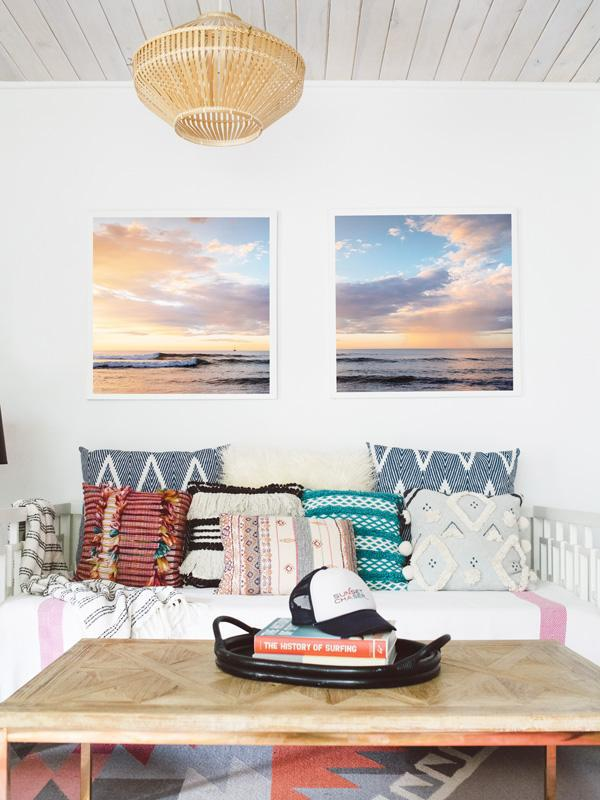 Boho chic living room with framed beach print. Beautiful pink rain and pastel sunset print. Anthropologie pillow, Urban Outfitters pillow, Target home decor, History of Surfing Book. Photographed by Samba to the Sea for The Sunset Shop.