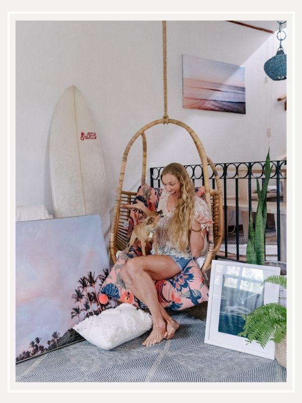 Destination Costa Rica photographer Kristen M. Brown and her Chihuahua Gidget at home with her sunset and beach photography prints. Boho surf shack in Tamarindo, Costa Rica. Samba to the Sea for The Sunset Shop.