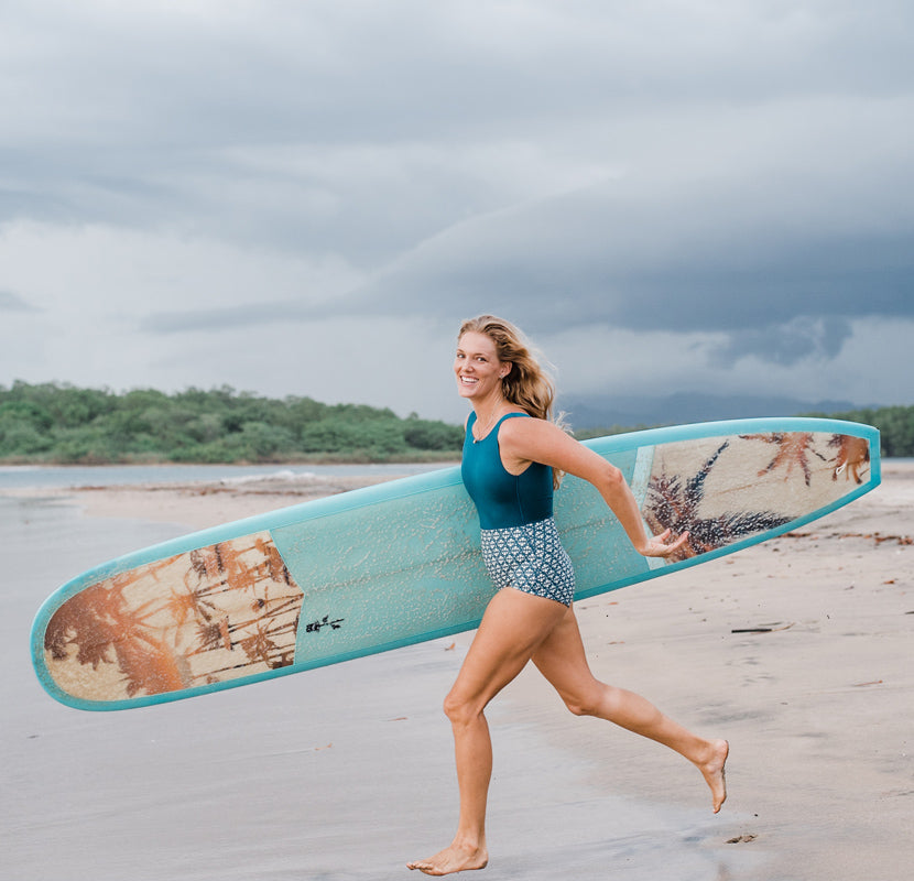 Photographer Kristen M. Brown of Samba to the Sea running on the beach with her surfboard to go surf in Tamarindo, Costa Rica.